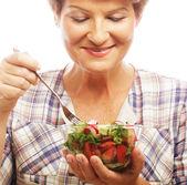 зрелые улыбается женщина, едят салат — Стоковое фото