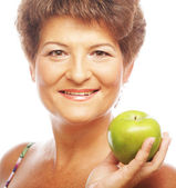 Mature smiling woman with green apple — Stock Photo