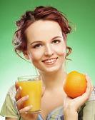 žena s pomerančová šťáva, zelené pozadí — Stock fotografie