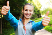 Smiling female fitness show thumbs up — Stock Photo