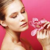 Mujer con flor de la orquídea — Foto de Stock