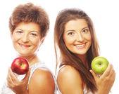 リンゴを保持している彼女の娘を持つ中年女性 — ストック写真