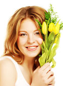 Young smiling woman with yellow tulips — Stock Photo