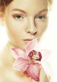 Vacker kvinna med rosa blomma — Stockfoto