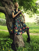 Young woman posing on a tree — Stock Photo