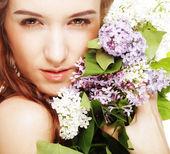 Lente meisje met lila bloemen. — Stockfoto