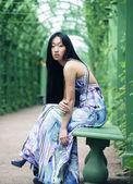 Aziatische vrouw zitten op de parkbank — Stockfoto