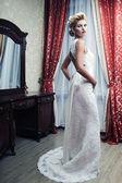 Happy bride posing in hotel room — Stock Photo