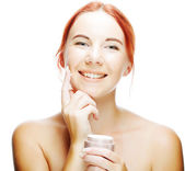 Smiling woman applying cream on her face — Stock Photo