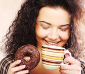 Woman holding donut and coffee — Zdjęcie stockowe