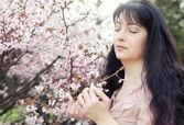 Brunette woman in spring flowers garden — Stockfoto