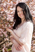 Happy young woman in spring flowers garden — Stock Photo
