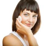 молодая женщина, применяя крем на ее лице — Стоковое фото