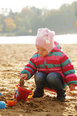 Little girl playing with sand at the autumn beach. — Stock Photo