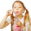 Funny lovely little girl blowing soap bubbles — Stock Photo #48046359