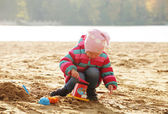 Little girl playing with sand at  beach — Stock Photo
