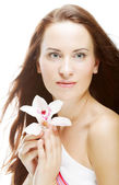 Woman with orchid flower — Stockfoto