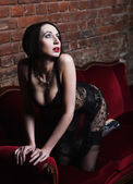 Brunette wearing black lingerie posing on chair — Stock Photo