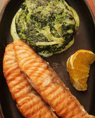 Salmon steak served with spinach — Stock Photo