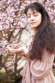 Woman in spring flowers garden — Stock Photo