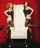 Two sexy women in lingerie on white throne — Stock Photo