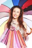 Vrouw met shopping tassen en paraplu — Stockfoto