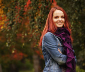Pretty woman relaxing in the autumn park — Stock Photo