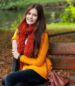 Girl on bench in autumn park — Stock Photo