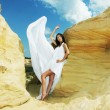 Woman in white dress dancing on the desert — Stock Photo #50362765