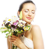 Beautiful young woman with bouquet flowers — Stock Photo