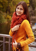 Young woman on bridge in autumn park — Stock Photo