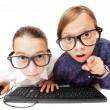 Young girls playing or working on a computer - Stock Photo