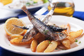 Grilled sardine fish with potato wedges — Stock Photo