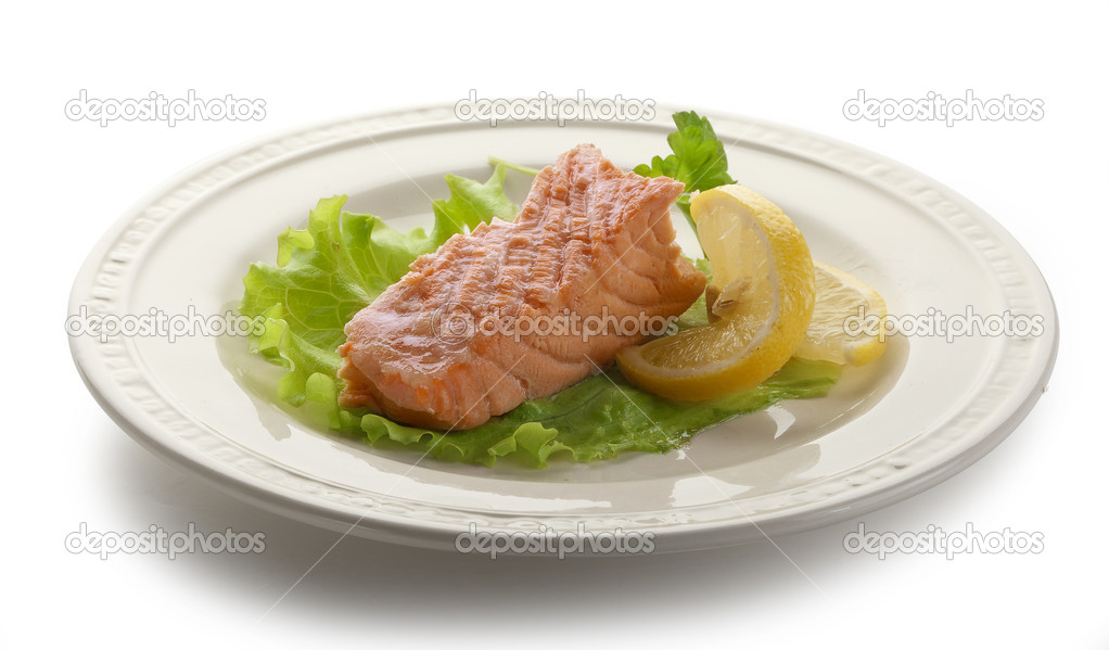Piece of steamed salmon with lemon and lettuce on the white plate — Stock Photo #16848849