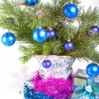 Fur-tree branches, a tinsel and a gift box - Stock Photo