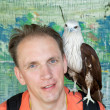 Portrait of the man with a prey bird on a shoulder. — Stock Photo