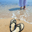 Beach slippers on sand, and female feet at a sea edge — Stock Photo #12681413