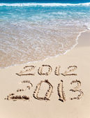 New 2013. The wave washes off an inscription 2012 — Stock Photo
