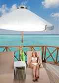 Jovem mulher tans num terraço da villa de água no oceano Maldivas — Fotografia Stock