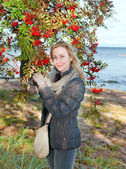 The young woman near red berries of a ripe mountain ash. — Stock Photo