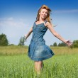 Happy young woman in the field of green ears — Stock Photo #13653499