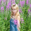 Stock Photo: Smiling young womwith bunch of willowherb flower in field
