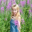 The smiling young woman with bunch of willowherb flower in the field — Stock Photo