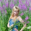 The smiling young woman with bunch of willowherb flower — Stockfoto
