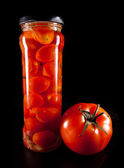 Canned tomatoes in glass jar and ripe tomato — Stock Photo
