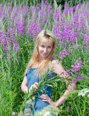 The smiling young woman with bunch of willowherb flower — Foto Stock