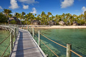View on tropical island from the wooden bridge to the coast over the sea. — Stock Photo