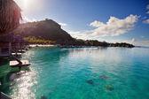 Ráno na tropickém ostrově. slunce stoupá za horou reed střechu boudy na oceán — Stock fotografie