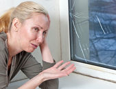 The housewife cries, bad quality double-glazed window has burst because of cold weather — Stock Photo