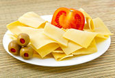 Macaroni products - a basis for a lasagna, with a tomato on a plate — Stock Photo